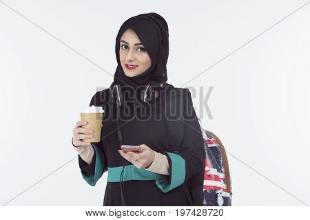 arab woman holding coffee cup and backpack