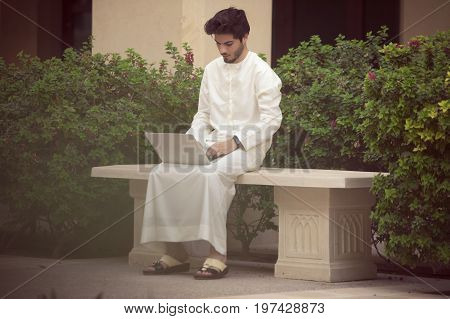 Arab young man working with his laptop outside