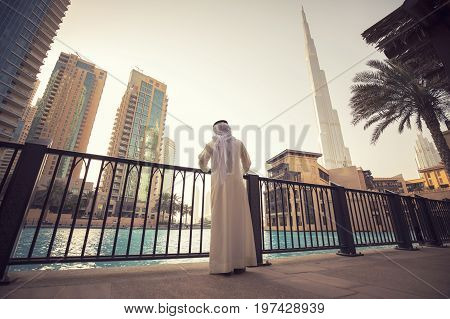 Arab man watching Dubai skyline evening time