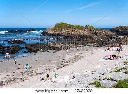 BALLINTOY, NORTHERN IRELAND, UK - JULY 17, 2017: The beach with people and rocks at Ballintoy harbor Northern coast of County Antrim Northern Ireland UK. The place featured in the Game of Thrones