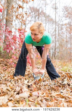 Young fit woman hunched over holding kettlebell in fallen leaves outside during autumn