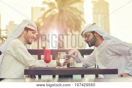 two Arab man talking . they sits at a table in a cafe and drink red juice at Dubai in evening