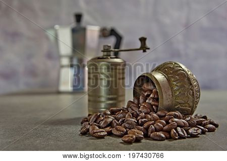 Small coffee grinder with coffee beans on the table and coffee maker on the back