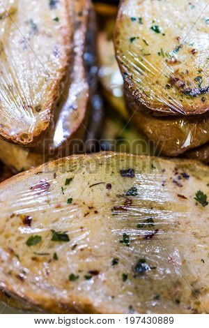 Plastic wrapped uncooked garlic bread loaves on display