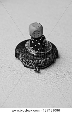 Black and gray dice on coins and a small purse
