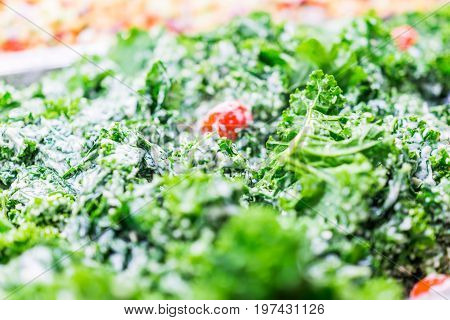 Green Kale Leaves And Tomatoes In Ceaser Salad Bar With Tongs