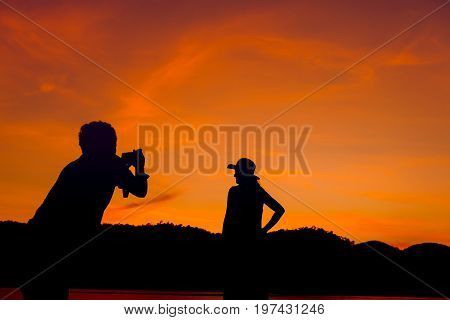 The photographer was posing for a model in the midst of an evening setting, with the orange light shining on the back so that they could see the silhouette of the couple in the dark.