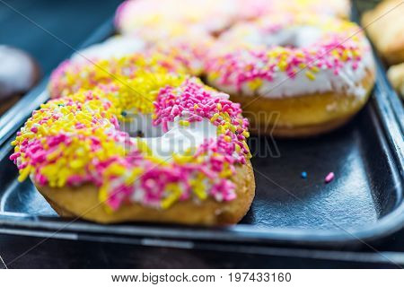 Vanilla White Iced Donuts With Pink And Yellow Sprinkles