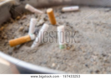Blurry Background of Cigarette butts dumped onto the cigarette trash can. Closed-up.