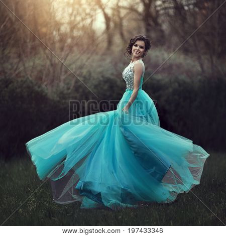 A beautiful graduate girl is spinning in a clearing in a blue dress. Elegant young woman in a beautiful dress in the park. Art photo.