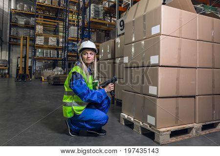 Blonde woman wearing blue uniform yellow jacket hardhat holding device looking away crouching in warehouse.
