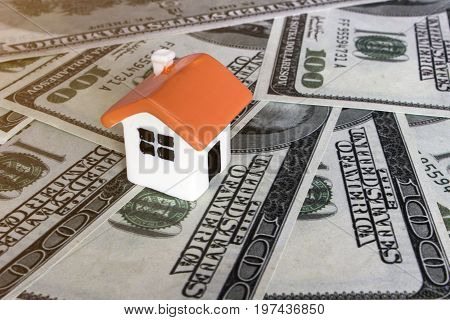 Doll house on background of banknotes close up