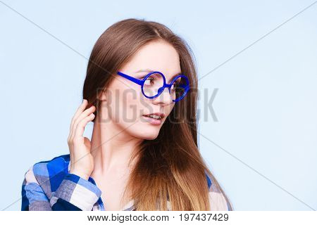Studying beauty of education and fun concept. Attractive nerdy woman in weird big glasses. Studio shot on blue background