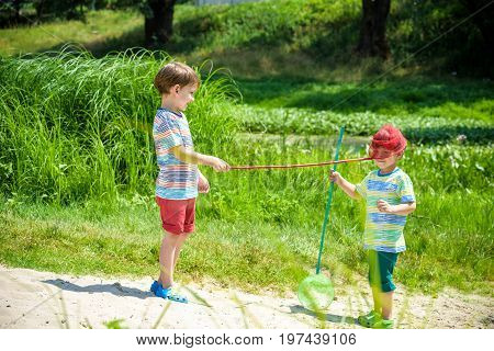 Two Little Sibling Brothers Playing With Scoop-net On The Meadow On Warm And Sunny Summer Or Spring