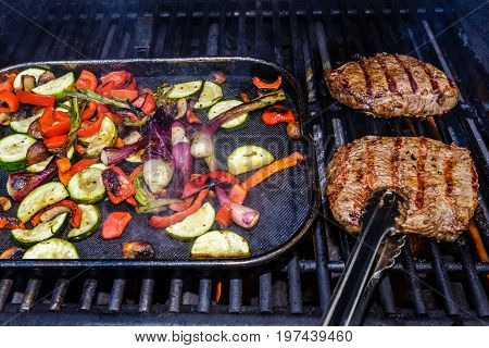Two steaks being grilled on the barbecue along with roasted vegetables. The vegetables include zucchini red bell pepper green onions and mushrooms. The steak is being show about to be flipped with a pair of tongs.