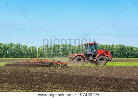 Tractor on the field plows the land Russia village summer