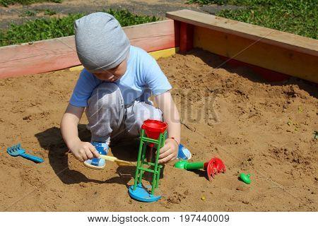 Little Boy Playing In The Sandbox.