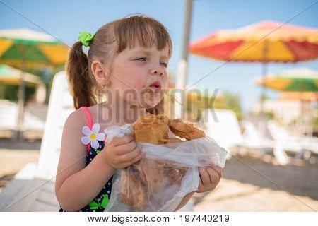 The little girl eats baklava dirty face summer vacation