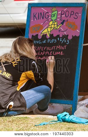 ATLANTA, GA - MARCH 2017:  A teenage girl writes menu items on a chalkboard for a popsicle company as she prepares for an event at Brook Run Park in Dunwoody GA on March 25 2017.