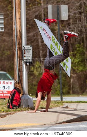 ATLANTA, GA - MARCH 2017: A young man skillfully balances a sign between his legs as he performs a cartwheel to promote a home selling event with signage on a street corner in Atlanta GA on March 25 2017 .