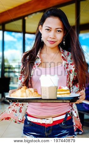Beautiful young girl taking lunch breack in outdoors cafe at summer day