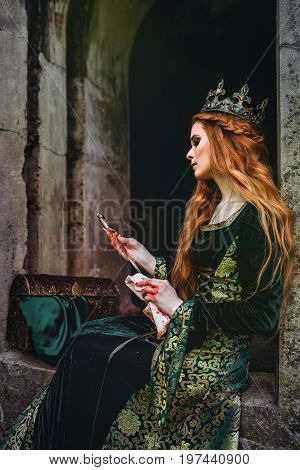 Red-haired woman in a green medieval dress near the castle