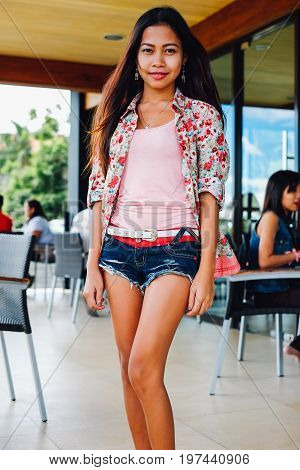 Beautiful young woman standing at the cafe