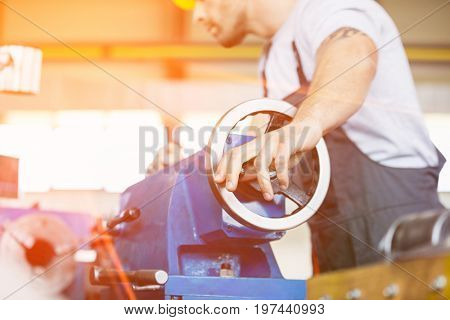 Low angle view of mid adult worker operating machinery in metal industry