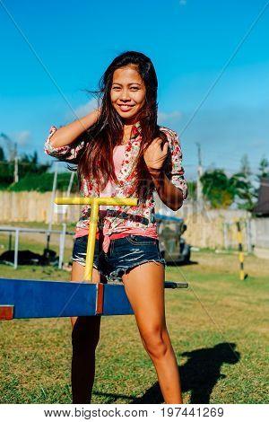 Beautiful young Asian woman swinging on swing