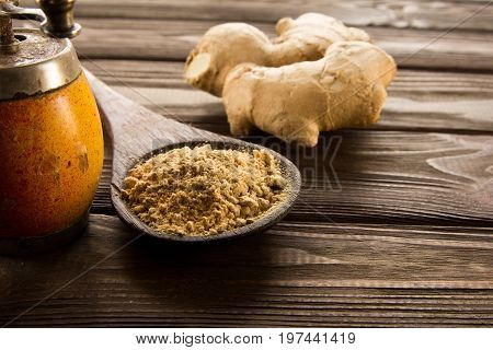 Spice ginger powder in wooden spoon on dark wooden background vintage hand mill and ginger root. Close-up.