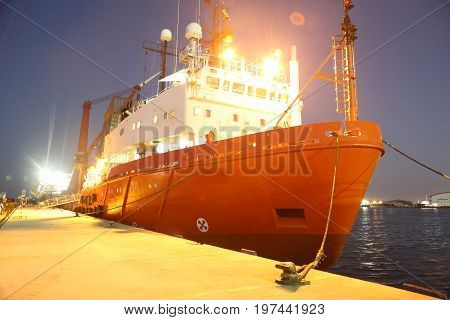 big red ship on the seashore side