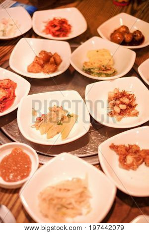 A traditional Korean restaurant with various side dishes. Korean meal side dishes of vegetable kinchi groundnuts garlic bean sprout seaweed