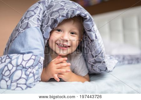 Baby boy hiding in parents bed