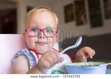 Little girl eat breakfast on the high chair