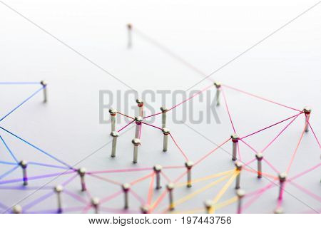 Linking entities. Networking, social media, SNS, internet communication abstract. Small network connected to a larger network. Web of red,orange yellow and blue wires on white background. Shallow DOF.