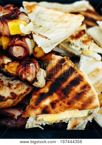 Grilled chicken meat skewers rolled with bacon. barbeque skewers with vegetables and roasted pizza bread.