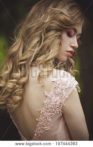 Portrait of a beautiful sensual blonde with protective eyes from the back. Girl with beautiful lips in a pink dress. Dress with neckline on back.