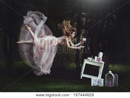 A beautiful blond girl is leaning with a mug of tea over a table. Lack of gravity. Like Alice in Wonderland. A girl with long hair flies like in a fairy tale.