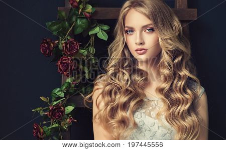 Blonde fashion  girl with long  and   shiny curly hair .  Beautiful  model  in light blue dress with wavy hairstyle . Dark Background flowers roses .