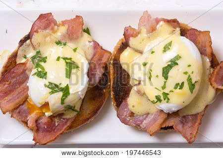 Eggs benedict with bacon on wooden background . Top view .