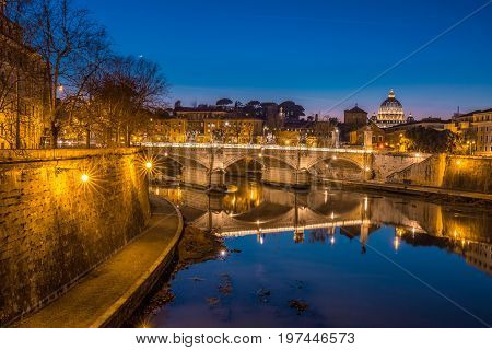 Blue hour view of St. Peters Basilica in the Vatican and the Ponte Sant'Angelo, Bridge of Angels, at the Castel Sant'Angelo and river Tiber in Rome, Italy.