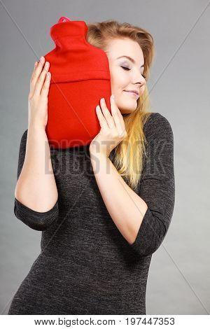 Woman Hugs Hot Water Bottle In Red Fleece Cover