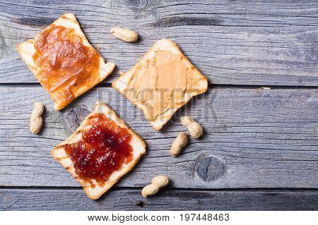 nut nougat cream with strawberry apricot jam and peanut butter sandwich