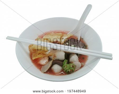 Pink seafood flat noodles with fish ball dumpling fish egg and special homemade red sauce serve on white bowl for Thai food and isolate background with clipping path. on white background