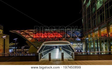 CANARY WHARF LONDON UK - 7 JANUARY 2016: Young couple walking through interesting geometric shapes and lines of new Crossrail Place tunnel walkway in Canary Wharf London's Docklands area at night