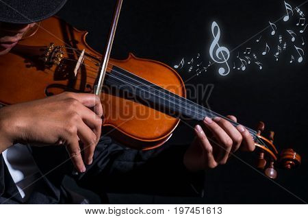 Close up Violin player in dark studio with music notes Musical concept