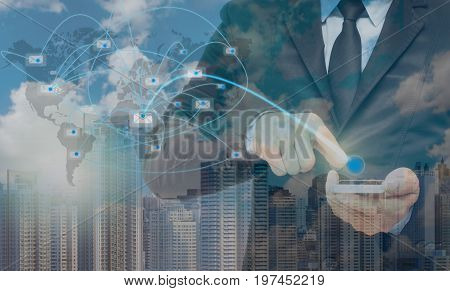 Double exposure of businessman using the smart phone with sending the email via network line on cityscape background business concept