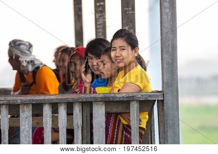 MANDALAY MYANMAR - MARCH 13 : Unidentified Burmese women smiling at the ubein bridge on March 13 2016 in Mandalay Myanmar. The U-Bein bridge is the longest teak bridge in the world 1.2km length.