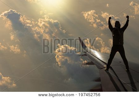 silhouette of man who show hands over the sun with clouds on airplane wing Challenge business concept