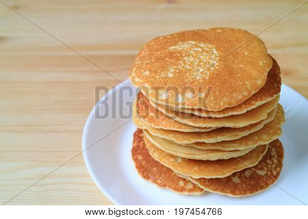 Stack of fresh homemade plain pancakes served on plate, blurred wooden table background with free space for text or design